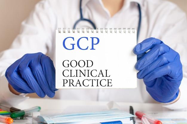 Manos de los médicos con guantes azules sosteniendo una hoja de papel con el texto gcp, abreviatura de buena práctica clínica.