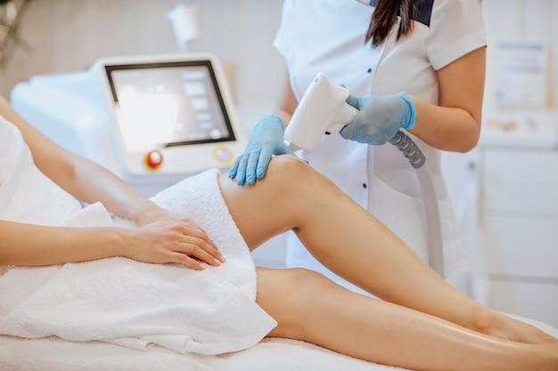 Manos de los médicos en guantes médicos azules sosteniendo una máquina de depilación y usándola en las piernas de la mujer
