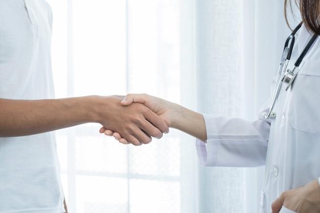 Manos de médicos y pacientes temblando después de discutir los resultados del examen de salud.