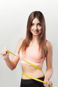 Manos para medir la cinta de la cintura. dieta. alimentación saludable. joven deportista. el concepto de salud y belleza.