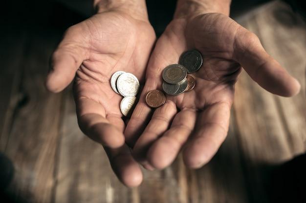 Manos de mendigo masculino buscando dinero en el piso de madera en la vía pública