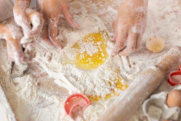 Manos mezclando harina y huevos para masa