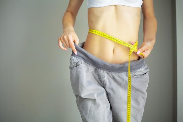 Manos midiendo la cintura con una cinta. mujer delgada y sana en su casa