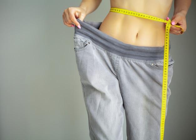 Manos midiendo la cintura con una cinta.