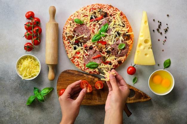 Las manos de la muchacha que preparan la pizza con albahaca se van en fondo gris claro.