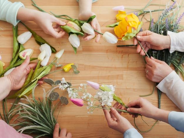 Manos de mujer alta vista con flores de primavera