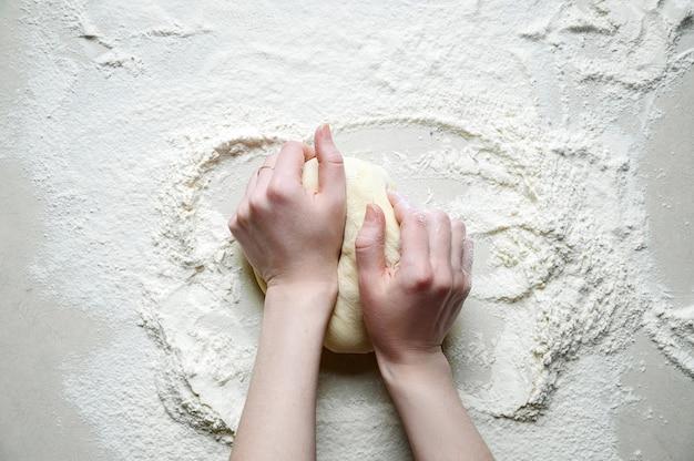 Manos de mujer amasa la masa con harina en la mesa de la cocina blanca. vista superior endecha plana.