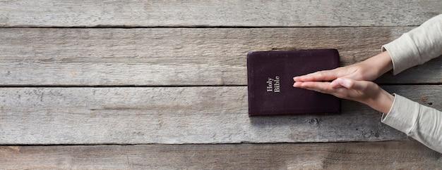 Manos de mujer en la biblia. ella está leyendo y orando sobre la biblia sobre la mesa de madera