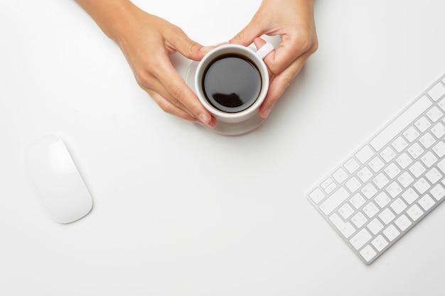 Manos de mujer, café y ratón.