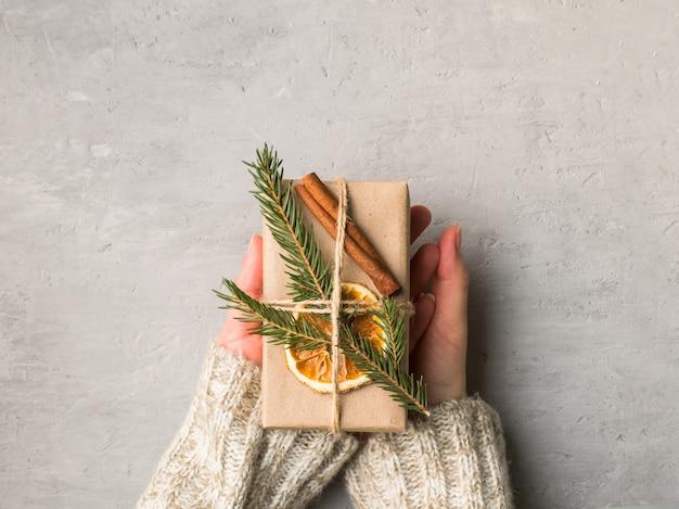 Manos de mujer con caja de regalo de navidad en hormigón gris