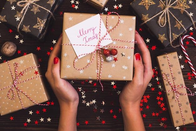 Manos de mujer con caja de regalo navideña con tarjeta postal feliz navidad en mesa festiva decorada