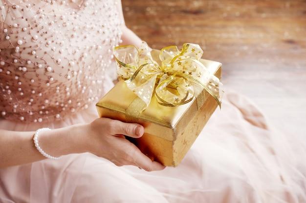 Manos de mujer con caja de regalo de oro.