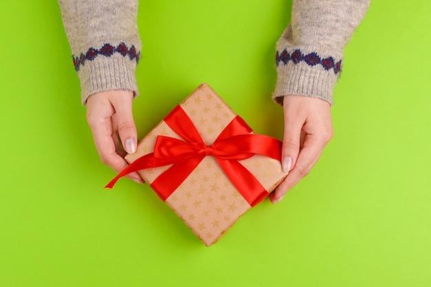 Manos de mujer con caja de regalo sobre fondo verde