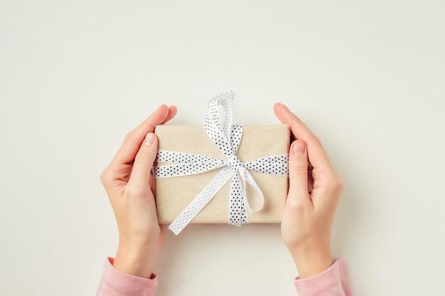 Manos de mujer con caja de regalo sobre una superficie blanca, vista superior