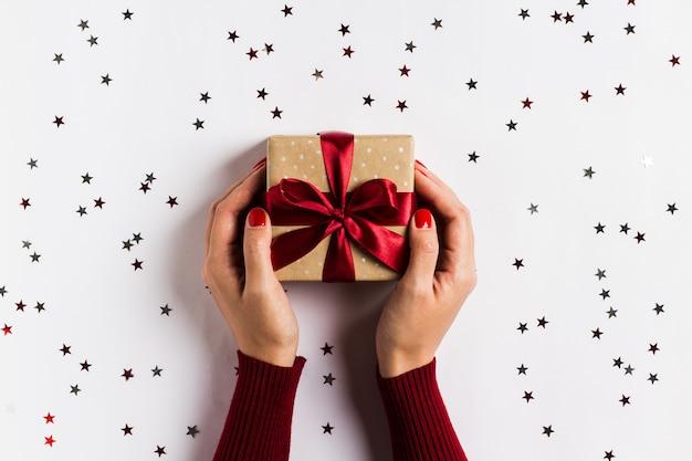 Manos de mujer con caja de regalo de vacaciones de navidad en mesa festiva decorada