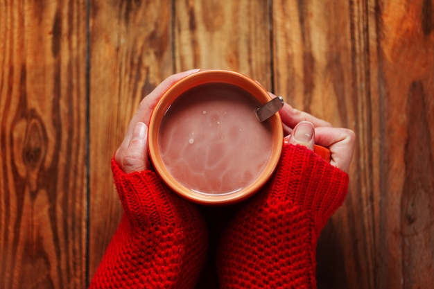 Manos de mujer en cálidos suéteres rojos con taza de café caliente en madera