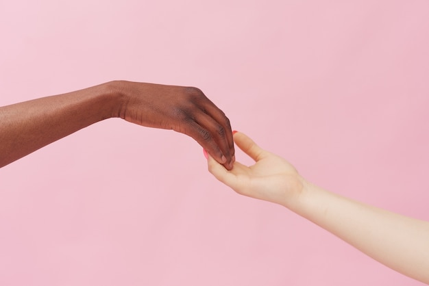 Manos de una mujer caucásica y un hombre afroamericano tocándose pueblo y unidad