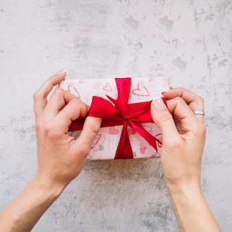 Manos de mujer cerca de caja actual en envoltura con cinta roja