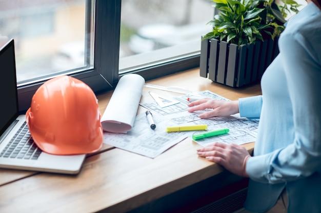 Manos de mujer cerca de dibujos de planos de construcción
