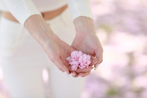 Las manos de la mujer de cerca. la mujer sostiene los pétalos de flores rosas en sus manos.