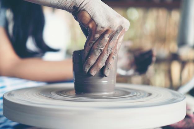 Las manos de la mujer se cierran, el magistral estudio de cerámica trabaja con arcilla