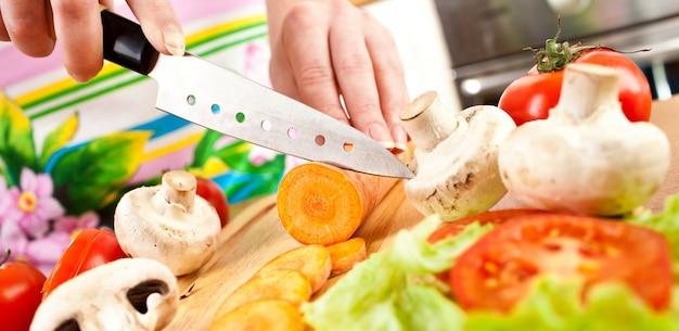 Manos de mujer cortando zanahoria, detrás de verduras frescas.