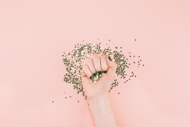 Manos de mujer cubiertas de estrellas doradas confeti en rosa