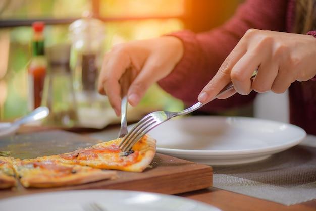 Manos de mujer con cuchara y tenedor tomando rebanadas de pizza.