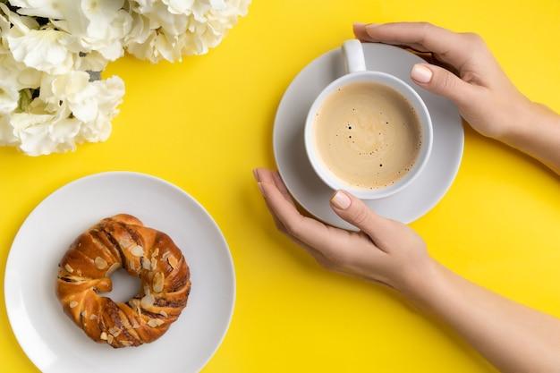 Manos de mujer cuidadas sosteniendo una taza de café sobre fondo amarillo. concepto de rama de lanzamiento de desayuno de primavera verano vista plana endecha superior.