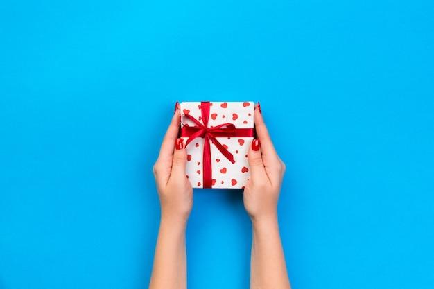 Manos de mujer dan caja presente