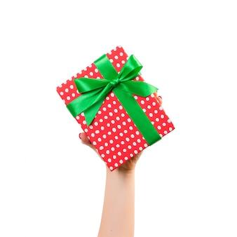 Manos de mujer dan navidad envuelta u otro regalo hecho a mano en papel rojo con cinta verde