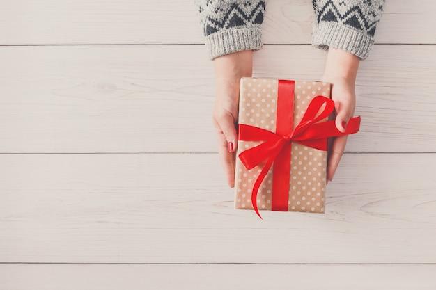 Las manos de la mujer dan navidad envuelto u otro regalo hecho a mano en papel con cinta roja.