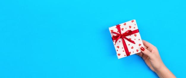 Las manos de la mujer dan el regalo envuelto hecho a mano de san valentín u otra fiesta en papel con cinta roja.