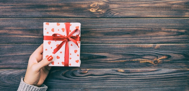 Manos de mujer dan regalo hecho a mano