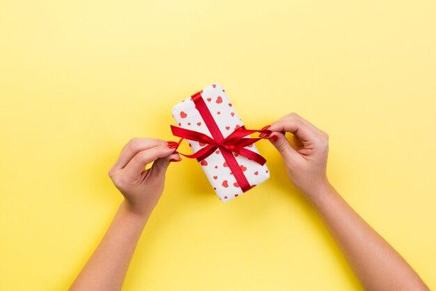 Las manos de la mujer dan el regalo de san valentín envuelto u otro regalo hecho a mano en papel rojo presente caja, decoración de corazón rojo de regalo en mesa amarilla, vista superior con espacio de copia para su diseño