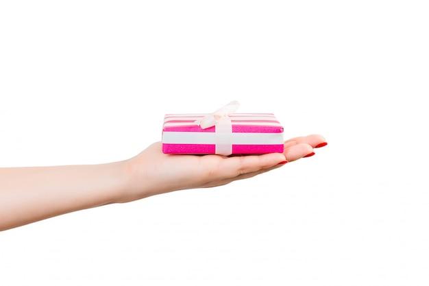 Las manos de mujer dan regalos navideños envueltos en navidad u otro regalo hecho a mano en papel rosa con cinta blanca