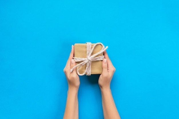 Las manos de la mujer dan a valentine envuelto u otro regalo hecho a mano de vacaciones en papel con cinta azul.