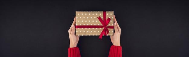 Manos de mujer dando caja de regalo de navidad sobre fondo negro
