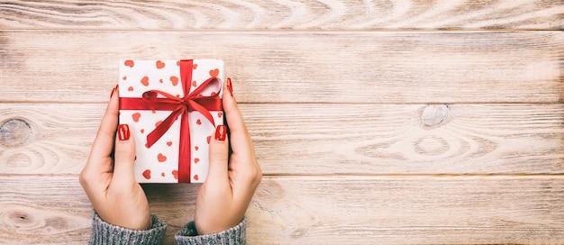 Manos de mujer dando caja de regalo de vacaciones en mesa de madera, caja actual, decoración de corazón rojo de regalo en mesa de madera, vista superior con espacio de copia para su diseño. banner web tonificado