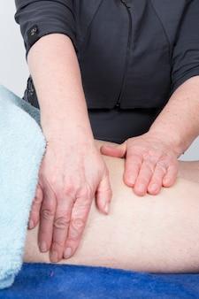 Manos de mujer dando masaje en la espalda de un hombre