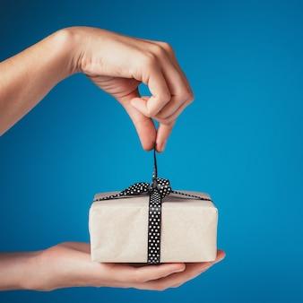 Las manos de la mujer desatan el arco en la caja de regalo en un fondo azul