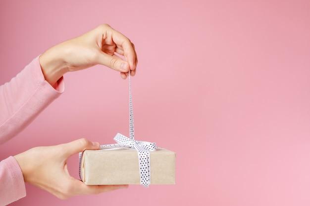 Las manos de la mujer desatan el arco en la caja de regalo en un fondo rosado