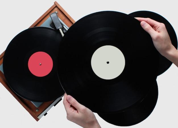 Manos de mujer con disco de vinilo, reproductor de vinilo con discos sobre fondo blanco. estilo retro, años 80, vista superior