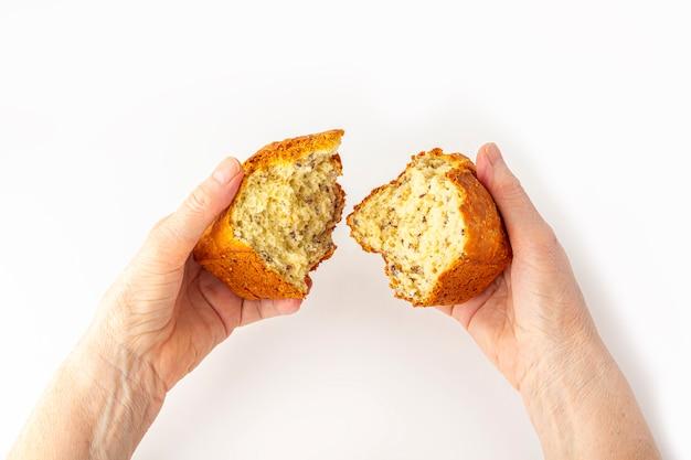 Las manos de la mujer de eldery sostienen (rompen) pequeño pan integral recién horneado de grano entero sobre fondo blanco. concepto de mano amiga, cerrar