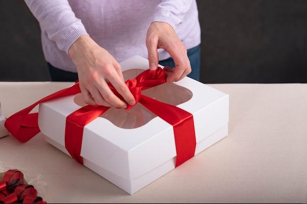 Manos de mujer está empacando regalos. caja blanca con cinta roja.
