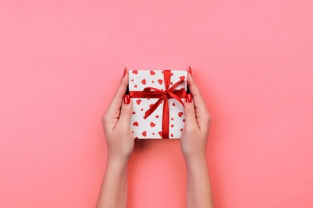 Manos de mujer envuelven regalo de san valentín u otro regalo hecho a mano en papel con cinta roja