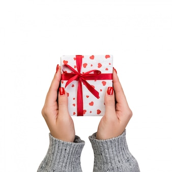 Las manos de mujer envuelven un regalo de san valentín u otro regalo hecho a mano en papel con cinta roja.
