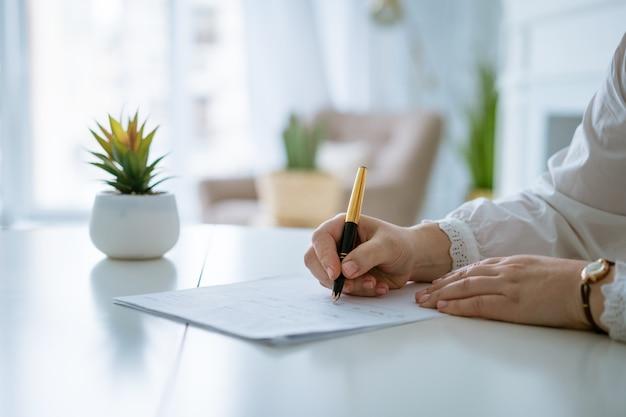 Manos de mujer escribiendo en hoja con un lápiz manos de empresaria trabajando con documentos