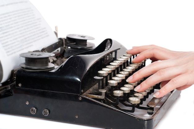 Manos de mujer escribiendo en máquina de escribir vintage aislado en blanco