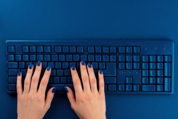 Manos de mujer escribiendo en el teclado de la computadora sobre fondo azul clásico, vista superior